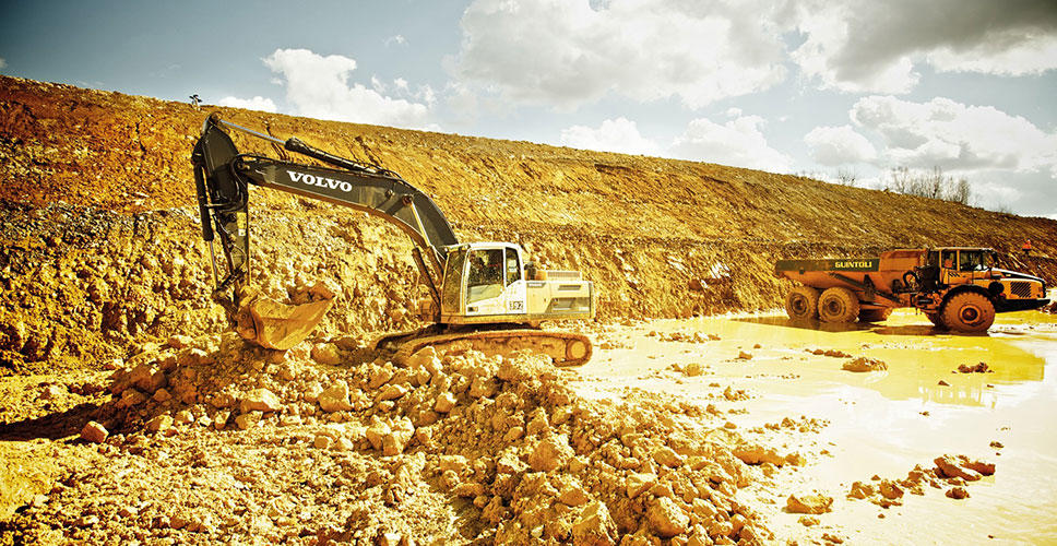 The Volvo excavator scoops up the excess earth and rock.