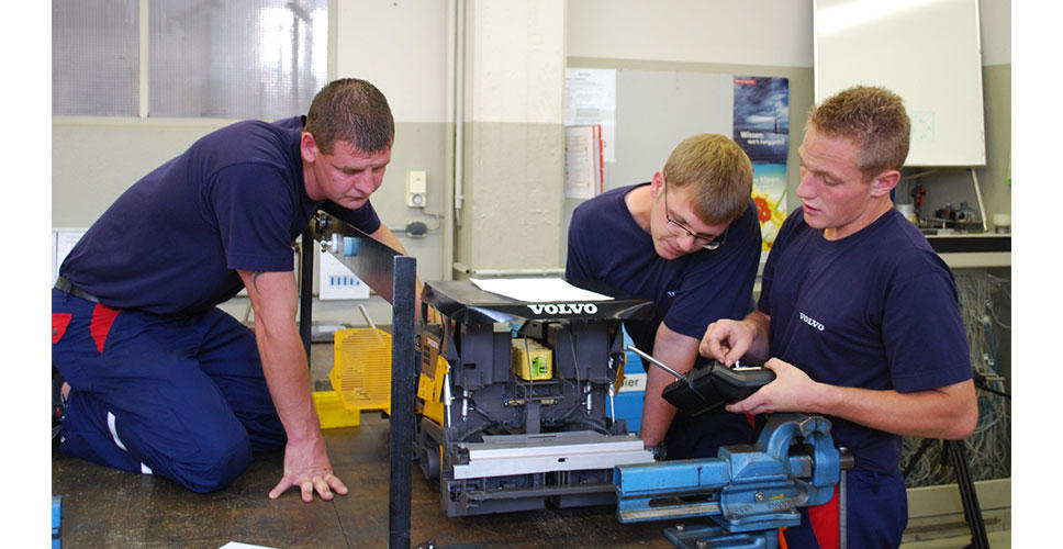 Two apprentices look at the electronic paver management panel at the screed of a Volvo ABG7820B tracked paver.