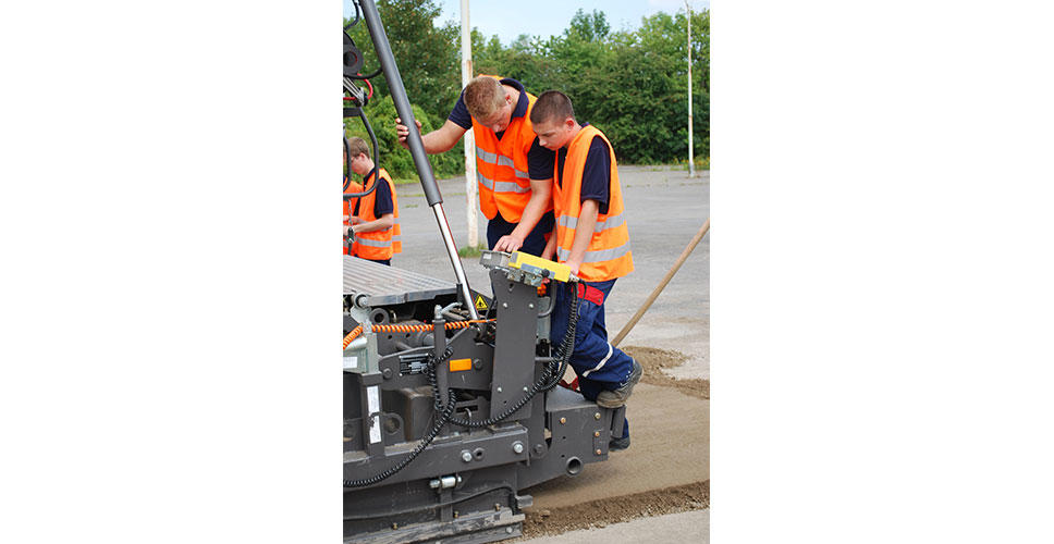 Two apprentices and an instructor operate a paver model.