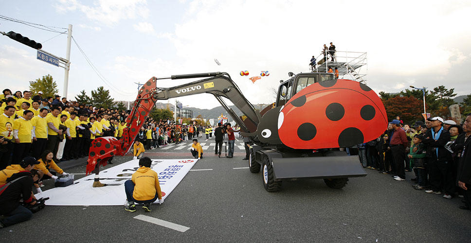 The ladybird-designed Volvo excavator paints a celebratory banner at the Changwon 2010 festival.