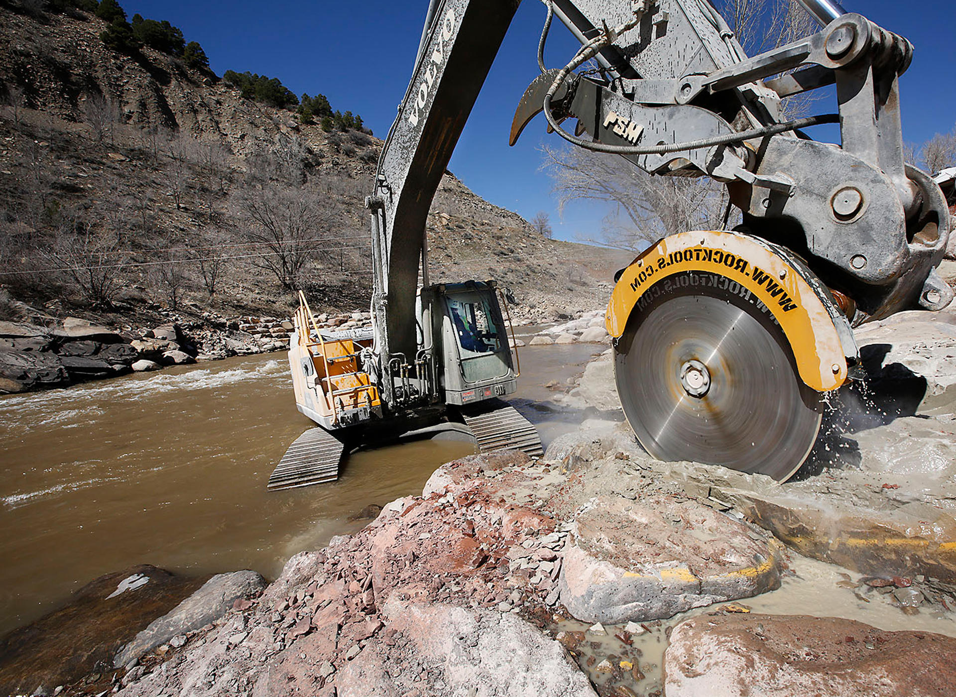 Volvo excavator saws through rock at Durango Whitewater Park in Colorado