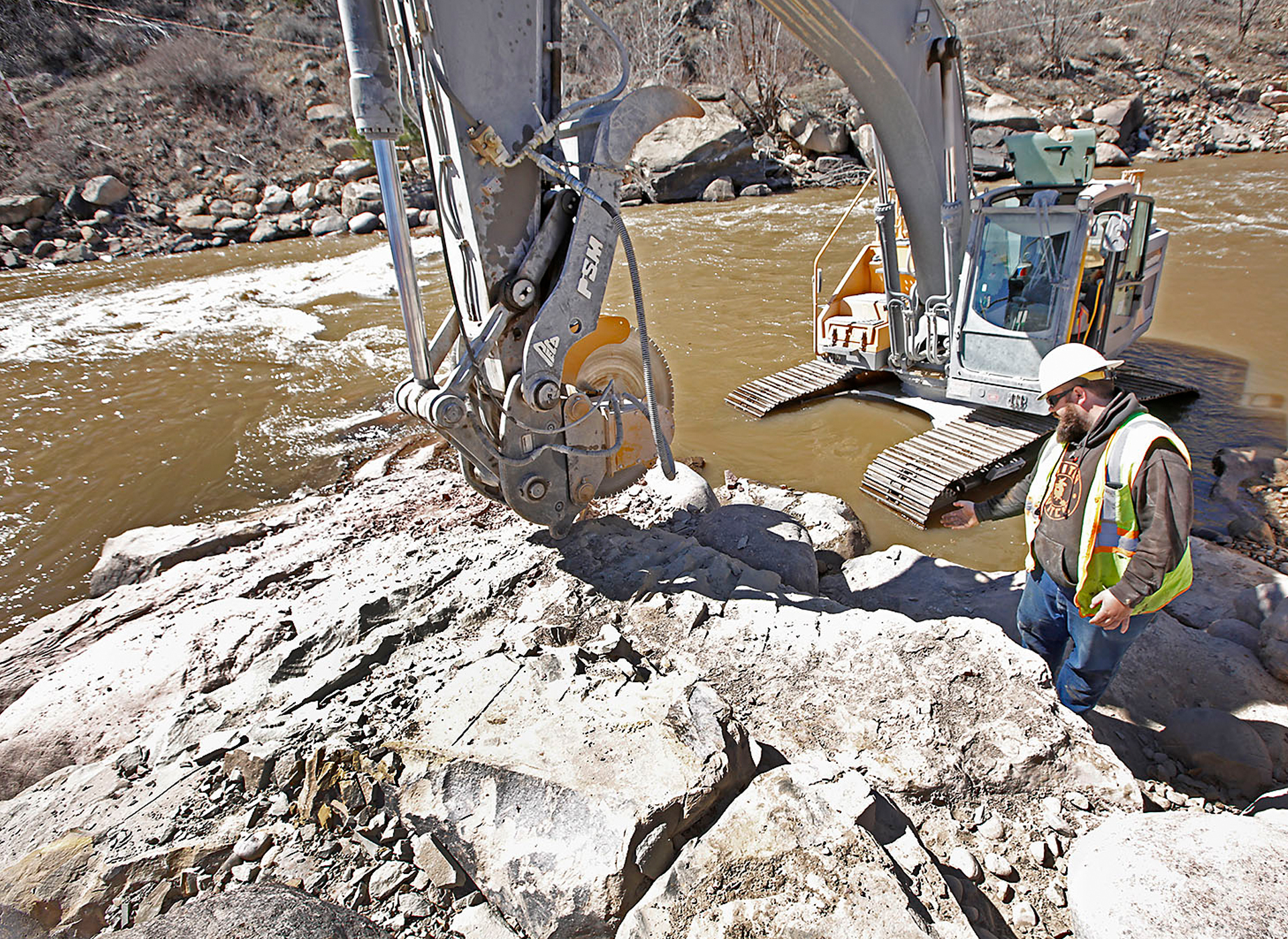 Volvo excavator saws through rock with percision at Durango Whitewater Park in Colorado