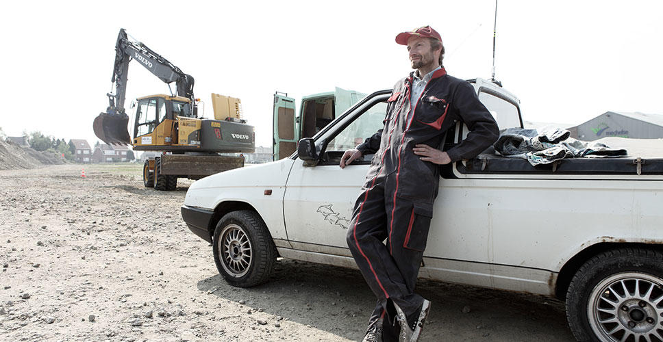 Peter Van den Eede as Zjempie, an employee of the Van As family's construction business, stands near a Volvo EW160C wheeled excavator.