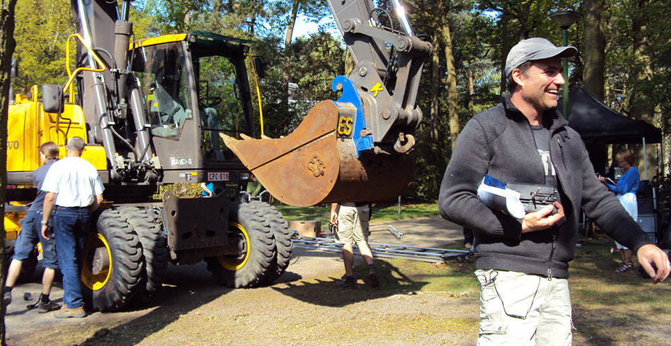 Crew members work near a Volvo EW160C wheeled excavator on the set of 'Zonen van Van As'.