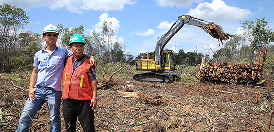 Owner of the Prima Kas Lestari company, Mansudin (right), poses in front of a working Volvo excavator with his son, Nico Jonathan